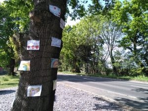 Children's artwork made in response to the pandemic adorns a tree in Botany Bay, Enfield