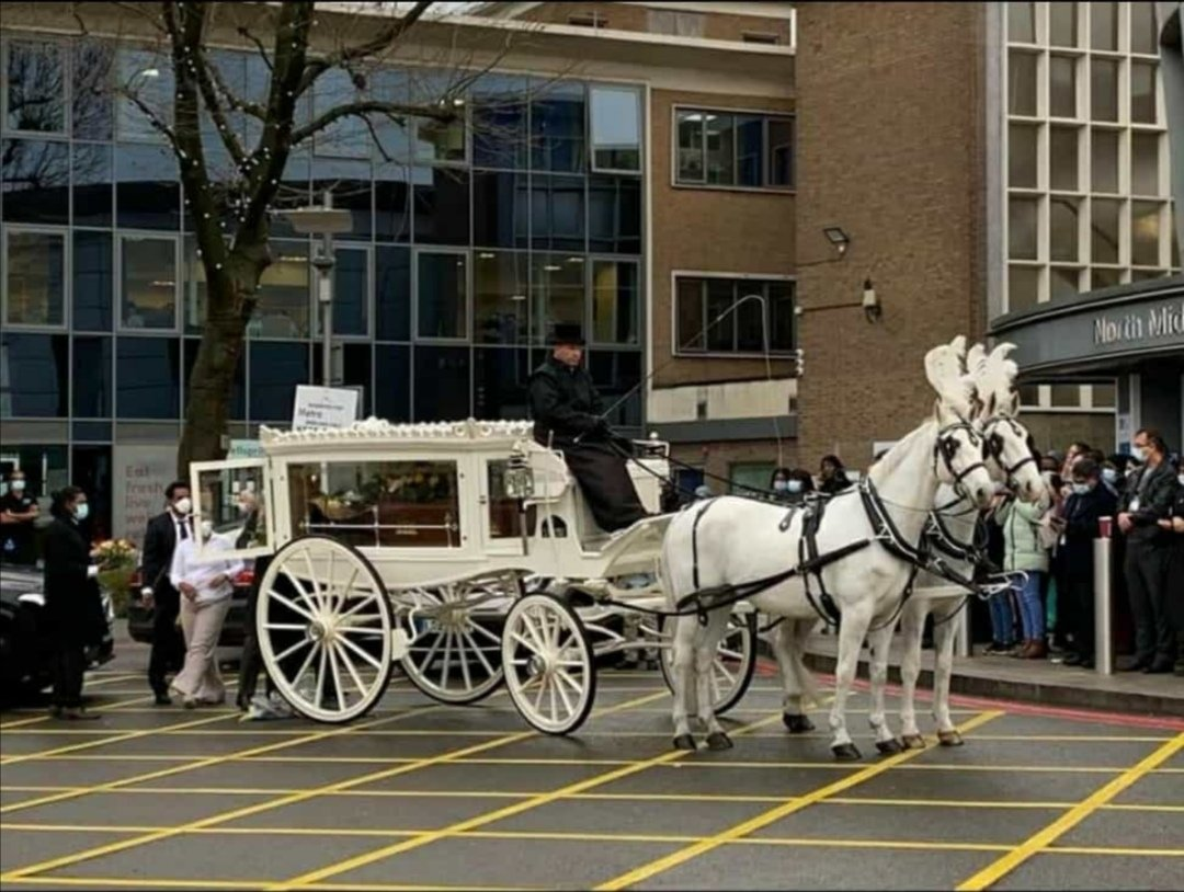 A horse-drawn carriage carrying Dr Malinda Dissanayanke's coffin stops outside North Middlesex Hospital