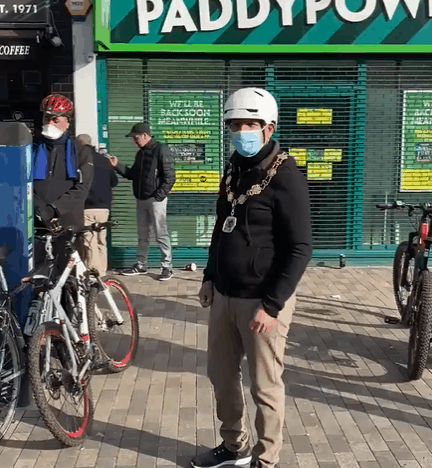 A still from the video posted on Twitter by Michael Skeggs shows Sabri Ozaydin wearing the mayoral chains of office while out on a bike ride with other councillors in Enfield