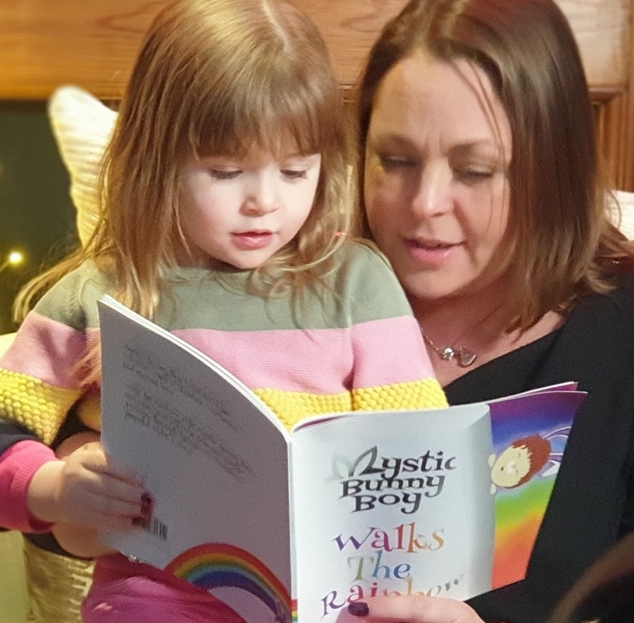 Jodie Webber reading her book Mystic Bunny Boy Walks the Rainbow to daughter Bobbie, who helped inspire it