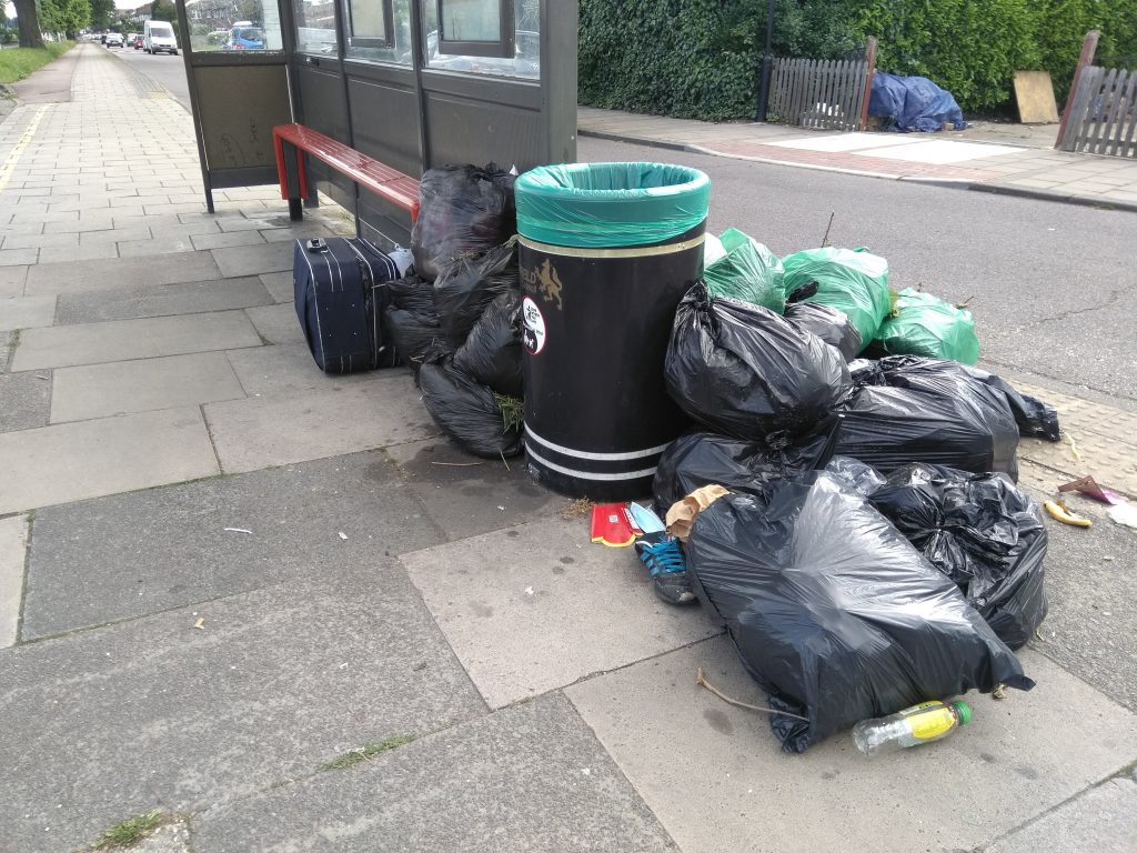 Black bags of litter piled up next to a bus stop in Great Cambridge Road, Enfield
