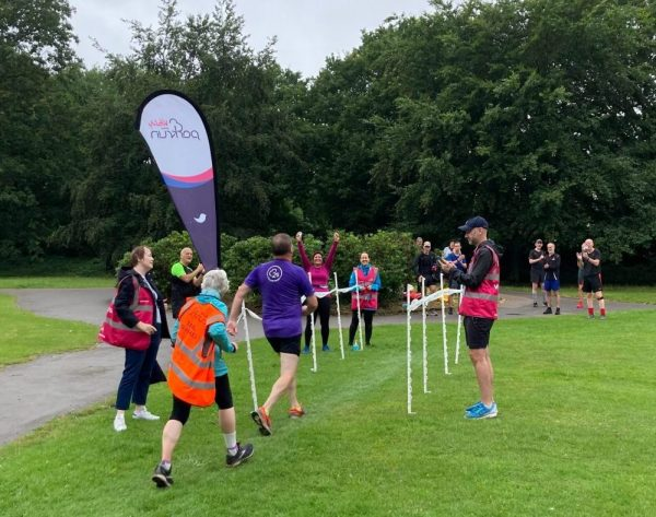 Runners cross the finish line for the Parkrun event at Grovelands Park, Southgate