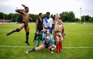 Enfield Town's babyface defender Jeremiah Gyebi falls victim to a sneak attack by NXT UK's dastardly heels at QE2 Stadium