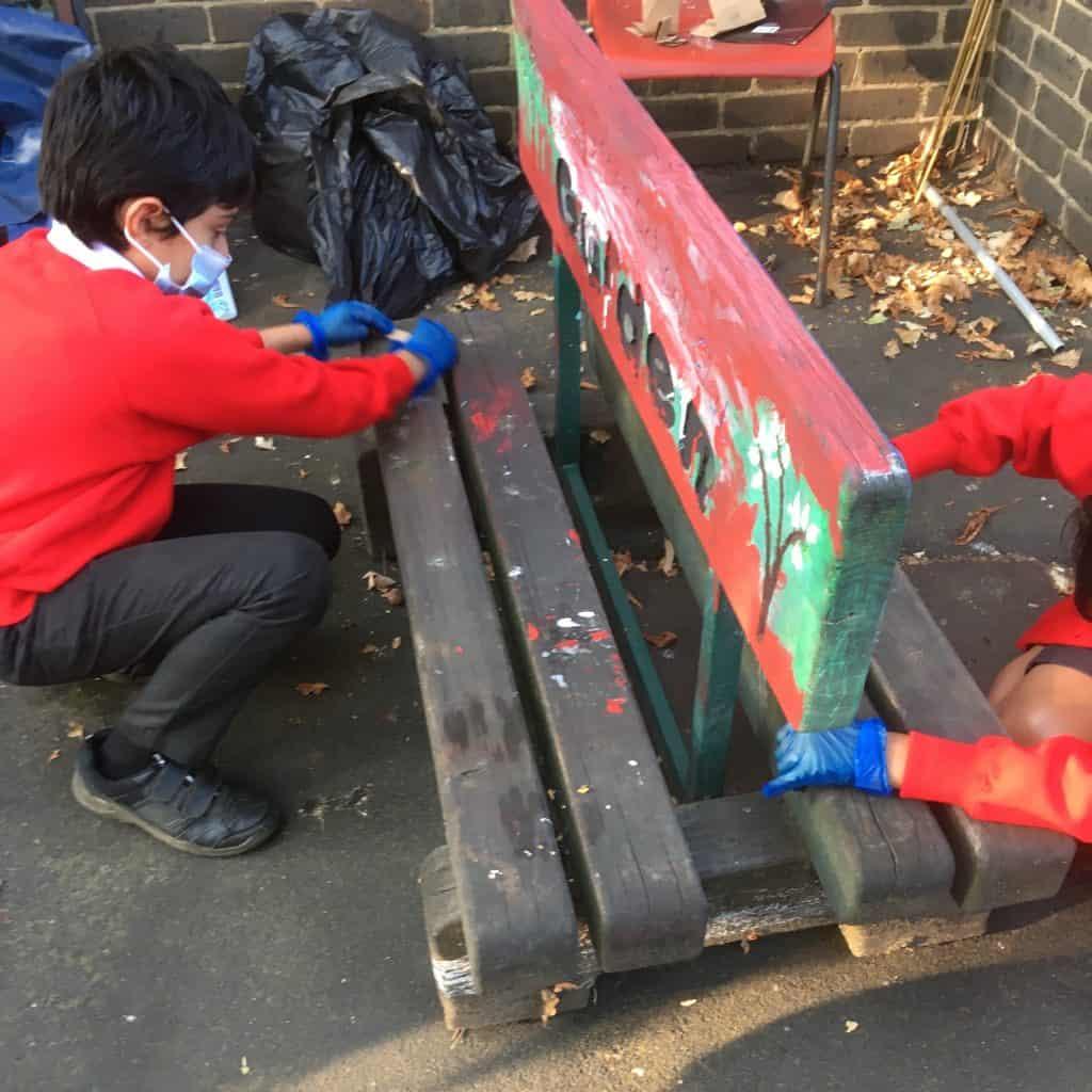Children from Walker Children's Club help paint a bench in the garden