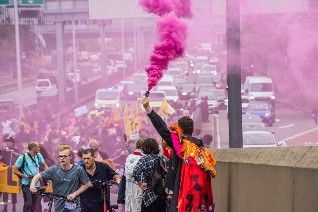 Pink flares were let off along the route of the protest march to Edmonton Eco Park, where a new incinerator is being built (credit Extinction Rebellion)