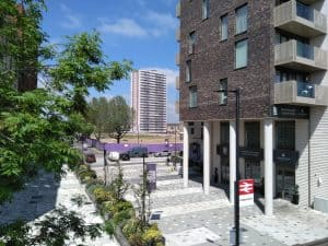 Only one of Alma Estate's four high-rise tower blocks remain standing (centre) as new housing (right) replaces it; the ongoing redevelopment will result in a significant net loss of social-rent housing on the Ponders End estate