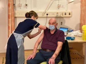 An elderly man receives a vaccine (credit NHS England)