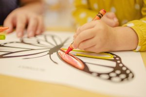 A child colouring in a butterfly